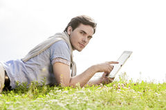 Side view of young man using digital tablet while lying on grass against clear sky Stock Images