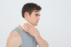 Side view of a young man wearing cervical collar. Over white background stock photos