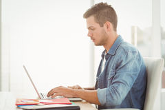 Side view of young man working on laptop Royalty Free Stock Image