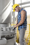 Side view of young manual worker using wrench on industrial machine Stock Photography