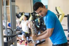 Young man exercising triceps pushdown during intense workout at the gym. Side view of a young men exhaling while exercising triceps pushdown at the rope cable stock image