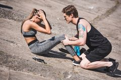 Man helping sportive woman with training. Side view of young men helping sportive women doing abs exercise Royalty Free Stock Photo