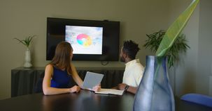 Side view of young mixed-race business team planning in conference room of modern office 4k stock footage