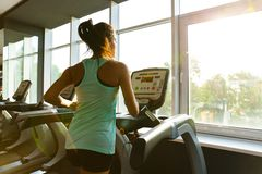 Side view of Young motivated sports woman running on treadmill stock image