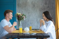 Side view of young multicultural couple having breakfast together. At home stock photo