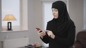 Side view of young muslim woman using social media on her smartphone. Smiling modern lady in hijab resting at home
