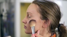 Side view of a young, pretty female model. Make up process. Artist putting some transparent, shiny rouge on woman`s stock video footage