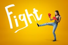 Side view of young pretty girl in jeans, sleeveless top and red boxing gloves with leg lifted for a kick on yellow. Background with Fight title. Show fighting stock images