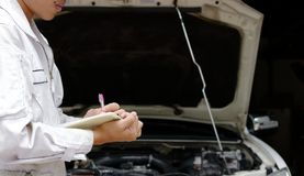 Side view of young professional mechanic in uniform writing on clipboard against car in open hood at the repair garage. Insurance. And maintenance service royalty free stock images