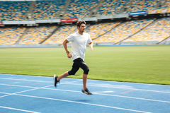 Side view of a young professional sprinter running. On racetrack Royalty Free Stock Photography