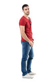Side view of young relaxed casual man in red t-shirt and jeans looking at camera Stock Photos