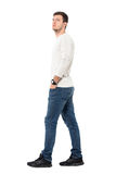 Side view of young relaxed casual man walking with hands in pockets looking up Stock Photo