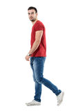 Side view of young relaxed casual man walking and looking at camera stock images