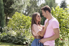 Side view of young romantic couple looking at each other in park Stock Photos