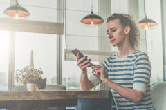 Side view,young serious woman in striped T-shirt sitting in cafe at wooden table in front of window and using smartphone Royalty Free Stock Photography