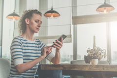 Side view,young serious woman in striped T-shirt sitting in cafe at wooden table in front of window and using smartphone Royalty Free Stock Photo