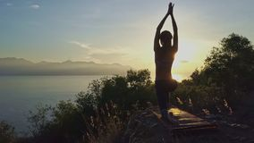 Side View Young Slim Athletic Woman in Yoga Pose on Rocky Slope. Among plants against sunrise above quiet ocean stock footage