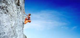 Young slim woman rock climber climbing on the cliff. Side view of young slim woman rock climber in bright orange pants climbing on the cliff. a woman climbs on a stock images