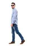 Side view of young smart casual man wearing sunglasses walking and looking at camera Royalty Free Stock Photo