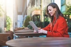 Side view.Young smiling attractive woman in orange coat is sitting outside in cafe at table and uses tablet computer. Royalty Free Stock Photos