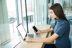 Side view of young smiling businesswoman sitting laptop at table in coffee shop and uses smartphone. Stock Image