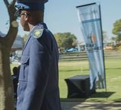 Side view of a young south african policeman wearing glasses. On a sunny day royalty free stock image