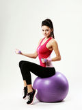 Side view of a young sport woman sitting on fitball with dumbells Stock Photography