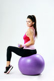 Side view of a young sport woman sitting on fitball with dumbells Stock Photo