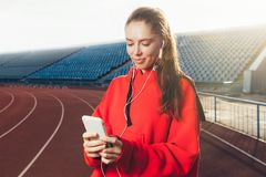 Side view of a young sport woman wearing a red hoodie. He is jogging and listening to music with his smartphone in hands. stock image