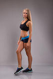 Side view of Young fitness woman looking to camera. over gray background Royalty Free Stock Photo