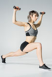 Side view of young sportswoman exercising with dumbbells Royalty Free Stock Photos