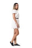 Side view of young stylish woman in white dress walking and looking at camera Stock Images