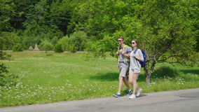 Side view: a young tourist couple walks along the road to beautiful mountains covered with forest. Active way of life. A young tourist couple walks along the stock video