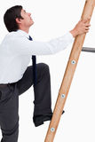 Side view of young tradesman climbing a ladder Stock Images