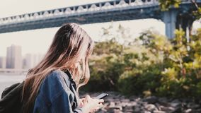 Side view of young traveler girl with backpack walking along calm Brooklyn Bridge river bank with smartphone slow motion stock footage
