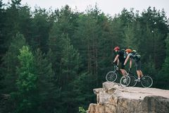 Side view of young trial bikers standing on rocky cliff with blurred pine forest on background and looking. At side royalty free stock photos
