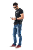 Side view of young undercover policeman typing message on mobile phone. Full body length portrait isolated on white studio background Royalty Free Stock Photo