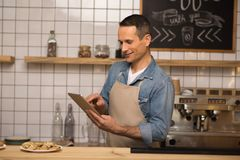 Waiter using digital tablet in cafe royalty free stock photography