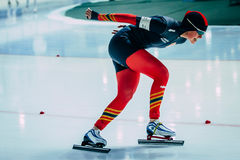 Side view young woman athlete speedskater goes around turn sprint distance Royalty Free Stock Image