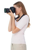 Side view of a young woman with camera Royalty Free Stock Photos