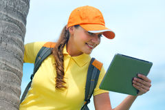 Side view of young woman in cap on the outdoor with  tablet comp Stock Photo