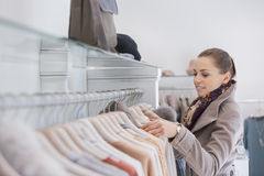 Side view of young woman choosing sweater in store Royalty Free Stock Photography