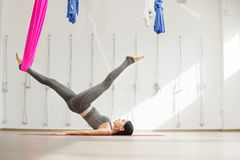 Side view of young woman doing antigravity yoga using hammock Stock Photos