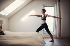 Side view of young woman doing exercise indoors in a bedroom. Copy space. stock images
