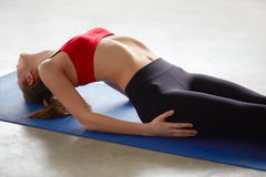 Side view of young woman doing half bridge pose Stock Photos