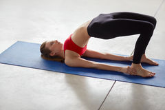 Side view of young woman doing half bridge pose Royalty Free Stock Image