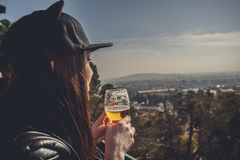 Side view of a young woman dressed standing and drinking alcohol. In the background landscape with aerial view, clouds in the sky. Girl uses the gadget Stock Photography