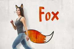 Side view of young woman in gray sleeveless top and blue jeans walking and smiling at camera against wall with fox ears. And tail adds-on and title Fox royalty free stock images