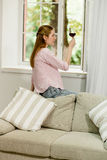 Side view of young woman at home, sitting on couch holding glass of wine. Royalty Free Stock Image