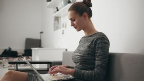 Side view of young woman at home sitting on the sofa, working with a laptop and typing text fast looking at the screen stock video footage